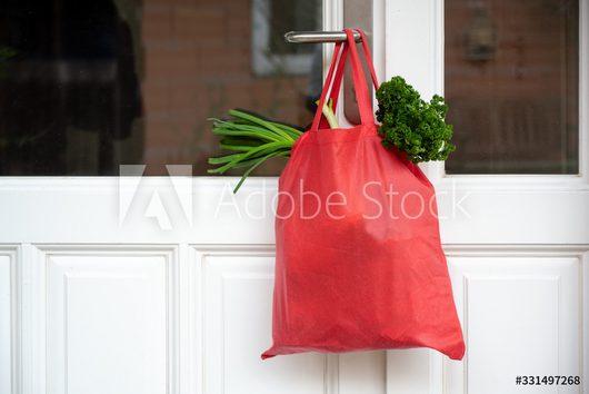 Nachbarschaftshilfe - Bild eines gefüllten Einkaufsbeutels der an der Türklinke hängt